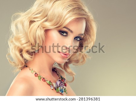 Beautiful cute girl with blonde curly hair with a necklace of precious stones - stock photo