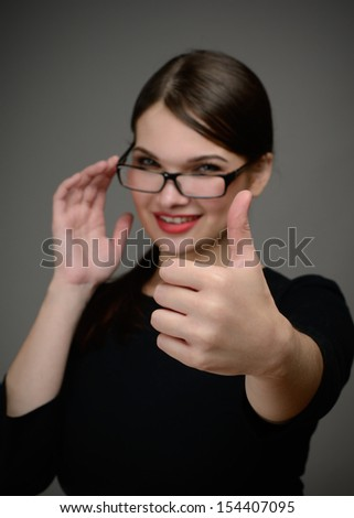 Beautiful cute girl with red lips and glasses showing thumb up