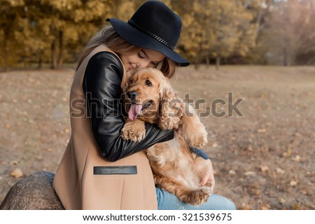 Beautiful cute happy girl in a black hat playing with her dog in a park in autumn another sunny day - stock photo