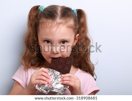 Beautiful cute kid girl eating dark healthy chocolate with fun look on blue background - stock photo