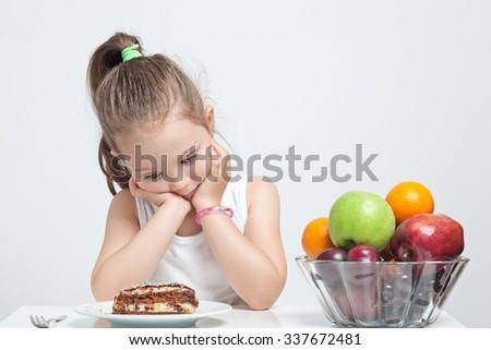 beautiful cute little girl choosing between cake and fruits - stock photo