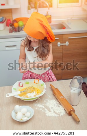 beautiful cute little girl with bonnet making pasta dough in kitchen