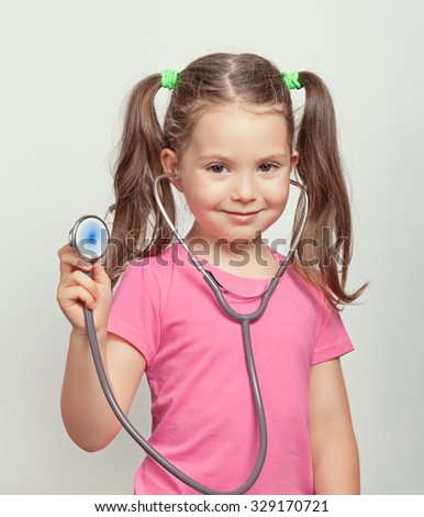 beautiful cute little girl with stethoscope. little girl playing in doctor. - stock photo