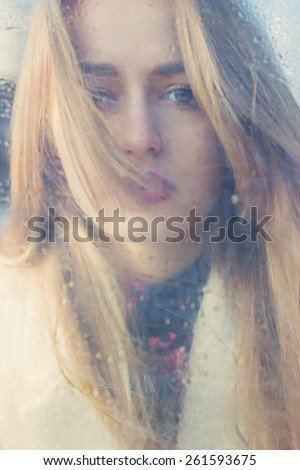 beautiful cute tender young girl with big sad eyes with white hair and dark lipstick in a bright coat looks into the camera through wet glass - stock photo