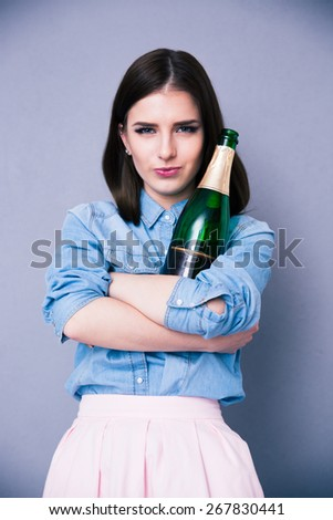 Beautiful cute woman holding bottle of champagne over gray background - stock photo