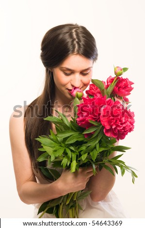 Beautiful cute woman smelling a red flowers - stock photo