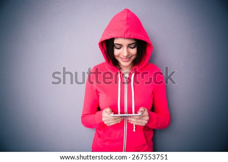 Beautiful cute woman using smartphone over gray background. Looking on smartphone. Wearing in pink jacket