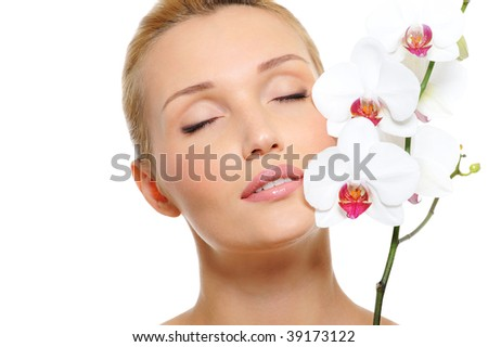 Beautiful cute young pretty woman with beautiful flower, orchid at face - stock photo