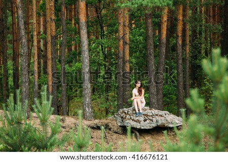 Beautiful Cute Young Woman Girl In White Dress Sitting On Stone In Summer Forest. Young Woman Looking In Right Side.