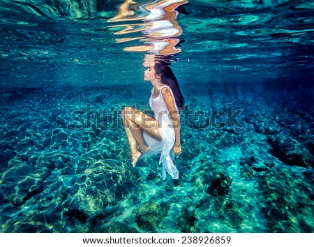 Beautiful dance underwater, gorgeous sportive woman wearing long white dress, dive to clear blue sea, zen balance and meditation concept - stock photo