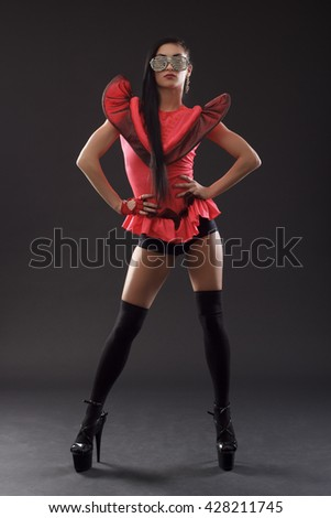 Beautiful dancer in stage costume in full growth on a black background .