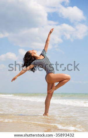 beautiful dancer posing on the sandy sea beach