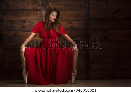 Beautiful dancer wearing red dress and perdorming contempopary dances. Attractive lady with long hair dancing in studio.