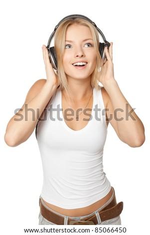 Beautiful dancing female in headphones while listening to the music over white background - stock photo