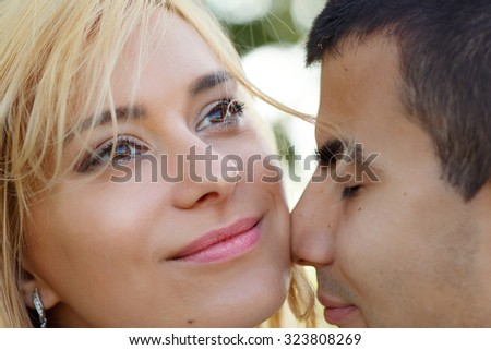 Beautiful dark eyed blonde bride and handsome groom romantic couple close-up - stock photo
