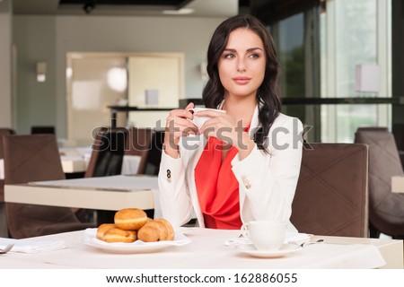 Beautiful dark hair woman sitting at the restaurant. Looking away drinking coffee  - stock photo