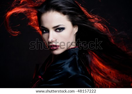 beautiful dark hair woman with hair in motion and red back light - stock photo