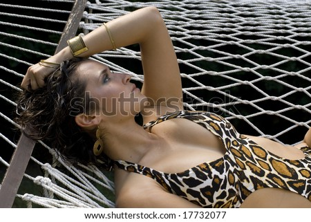 Beautiful dark-haired female posing on her back in a print swimsuit - stock photo