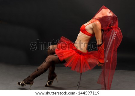 Beautiful dark-haired girl in a red wedding dress isolated on black background in studio