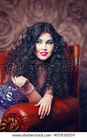 Beautiful dark-haired girl in a short sexy purple dress sits in the big chair kozhanolm, cocktail party, bachelorette party - stock photo