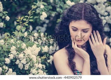 Beautiful dark-haired girl with long hair in the lush spring garden, closeup portraites - stock photo