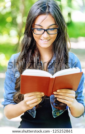 Beautiful dark-haired smiling young woman in glasses reads red book, against background of summer green park.