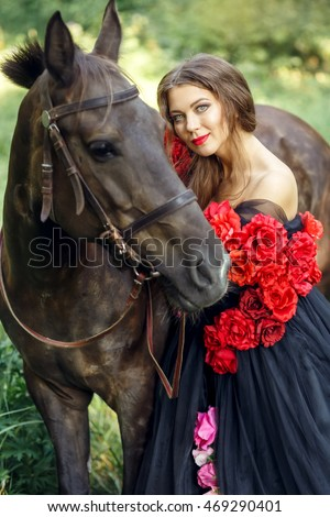 Beautiful dark haired women hugging brown horse in summer park wearing long black dress decorated with flowers.