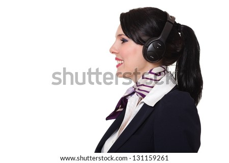 Beautiful dark haired young business woman dressed in a dark blue suit with a purple scarf and white shirt standing smiling and wearing earphones looking towards left, isolated on white background