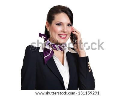 Beautiful dark haired young business woman dressed in a dark blue suit with a purple scarf smiling and talking to desktop phone held in her left hand, isolated on white background - stock photo