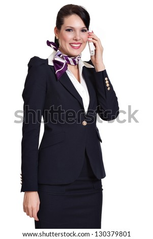 Beautiful dark haired young business woman dressed in a dark blue suit with a purple scarf standing smiling and talking to the phone held in her left hand, isolated on white background - stock photo