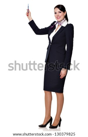 Beautiful dark haired young business woman dressed in a navy suit with a purple scarf and white shirt standing smiling and holding a pen in her lifted right hand, isolated on white background - stock photo