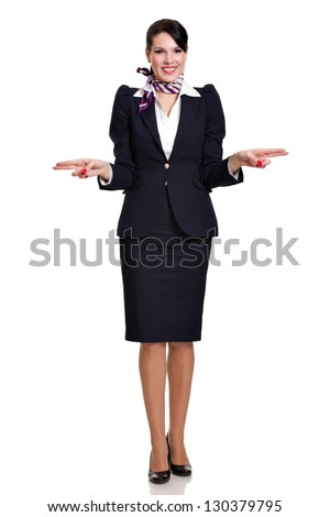 Beautiful dark haired young steward woman dressed in a dark blue suit with a purple scarf standing and showing the side exits of a plane, isolated on white background - stock photo