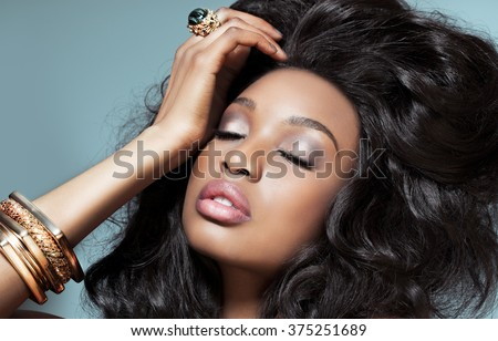 Beautiful dark model with golden jewelry over cyan background. Fashion and beauty with African dark skin model. - stock photo