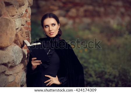 Beautiful Dark Princess Reading a Book - Portrait of gothic queen outside with storybook