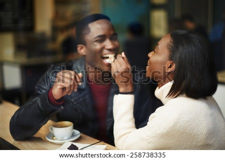 Beautiful dark skinned couple in love having a great time together, man and woman enjoying each other, young woman feeding man with dessert cake at their dating - stock photo
