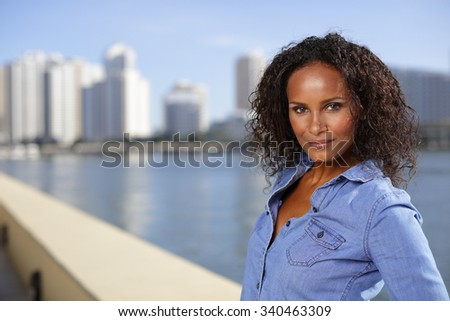 Beautiful dark skinned woman by the bay - stock photo