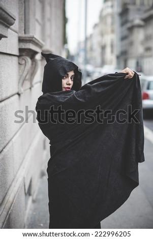 beautiful dark vampire woman with black mantle and hood halloween - stock photo