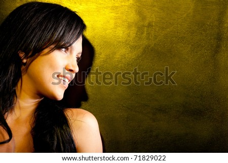 Beautiful dark woman smiling over a yellow background - stock photo