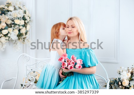 beautiful daughter kissing her mother on the cheek. a bouquet of pink tulips, Mother's Day, 8 March - stock photo