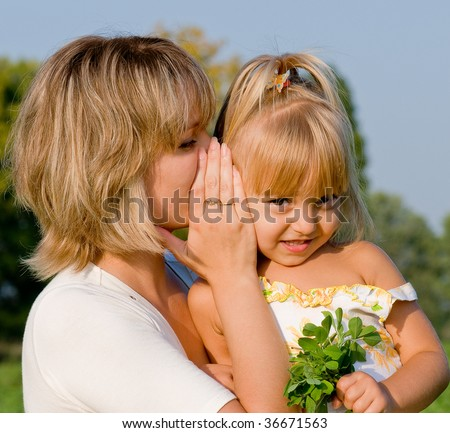 Beautiful daughter listening to her mother's secret whispers - stock photo