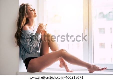 Beautiful daydreamer. Beautiful young woman holding coffee cup and keeping eyes closed with smile while sitting at windowsill at home - stock photo