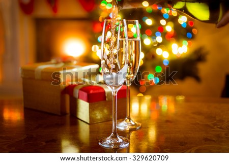 Beautiful decorated dinning table for Christmas with glasses of champagne - stock photo