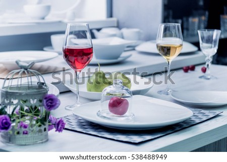 Beautiful decorated table. Wine, food and flowers. Light background