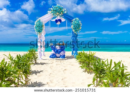 beautiful decorated wedding arch on sand beach, outdoor tropical wedding setup and venue - stock photo