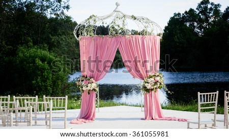 Beautiful decorated with light fabric of chiffon and bouquets of roses pastel colors pavilion and table standing on green grass near lake and trees sunny day - stock photo