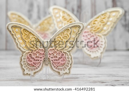 Beautiful decorative butterflies on white wooden background - stock photo