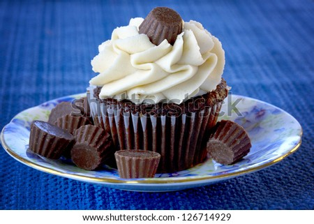 Beautiful, delicious chocolate cupcake with candies sitting on blue floral place and blue placemat - stock photo