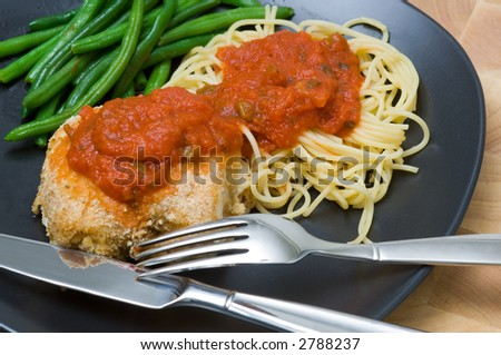 Beautiful delicious dinner including pasta chicken and green beans on a black plate with flatware