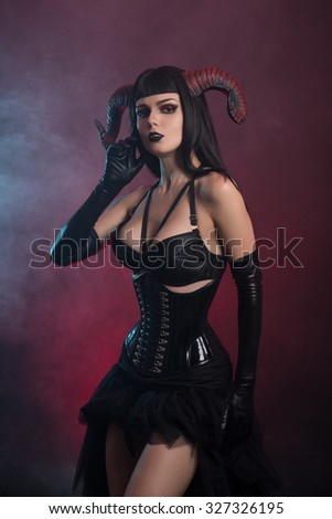 Beautiful demonic girl with horns wearing corset, Halloween theme  - stock photo