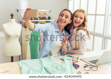 Beautiful designers are making selfie using a smart phone and smiling while working in dressmaking studio. Hand with phone in focus - stock photo